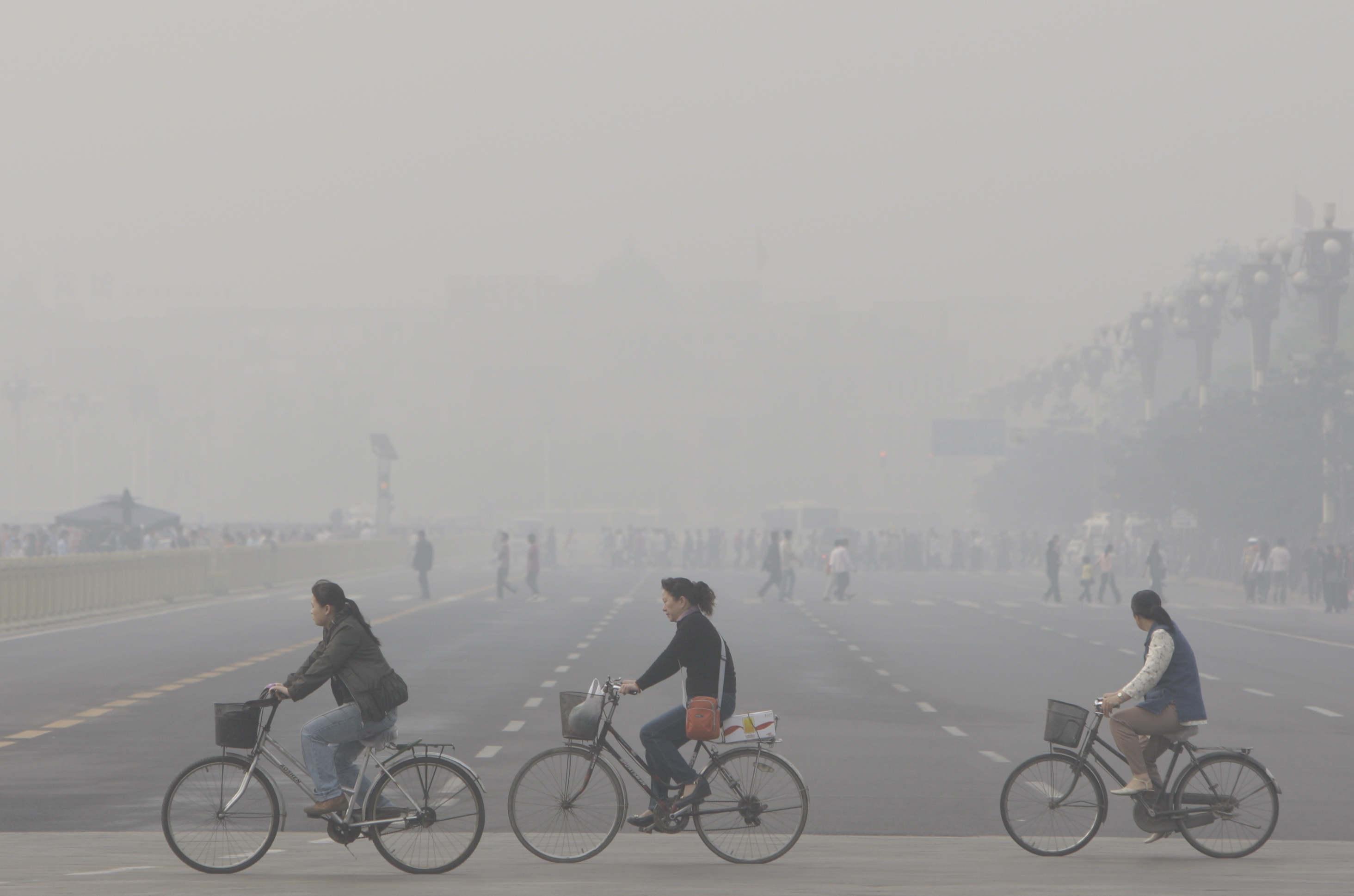 **FILE**This May 1, 2008 file photo shows Chinese women cycling through smog and pollution over Beijing's Tiananmen Square. A thick brown cloud of soot, particles and chemicals stretching from the Persian Gulf to Asia threatens health and food supplies in the world, according to a report commissioned by the U.N. Environment Program released Thursday, Nov. 13, 2008. (AP Photo/Oded Balilty, File)