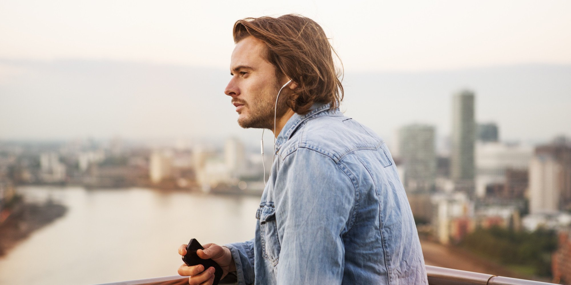 Man listening to music ovelooking city.