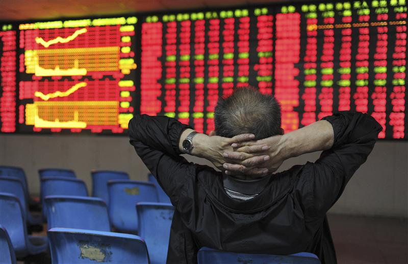 An investor places his hands on the back of his head in front of an electronic board showing stock information at a brokerage house in Hefei, Anhui province May 2, 2012. China shares climbed 1.8 percent to their highest closing level in seven weeks on Wednesday, after the country's securities regulator said it would reduce transaction fees for trades on the Shanghai and Shenzhen stock exchanges. REUTERS/Stringer (CHINA - Tags: BUSINESS)