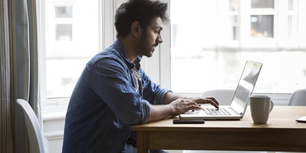 banking-blog-young-man-sitting-at-a-table-near-windows-looking-at-a-laptop