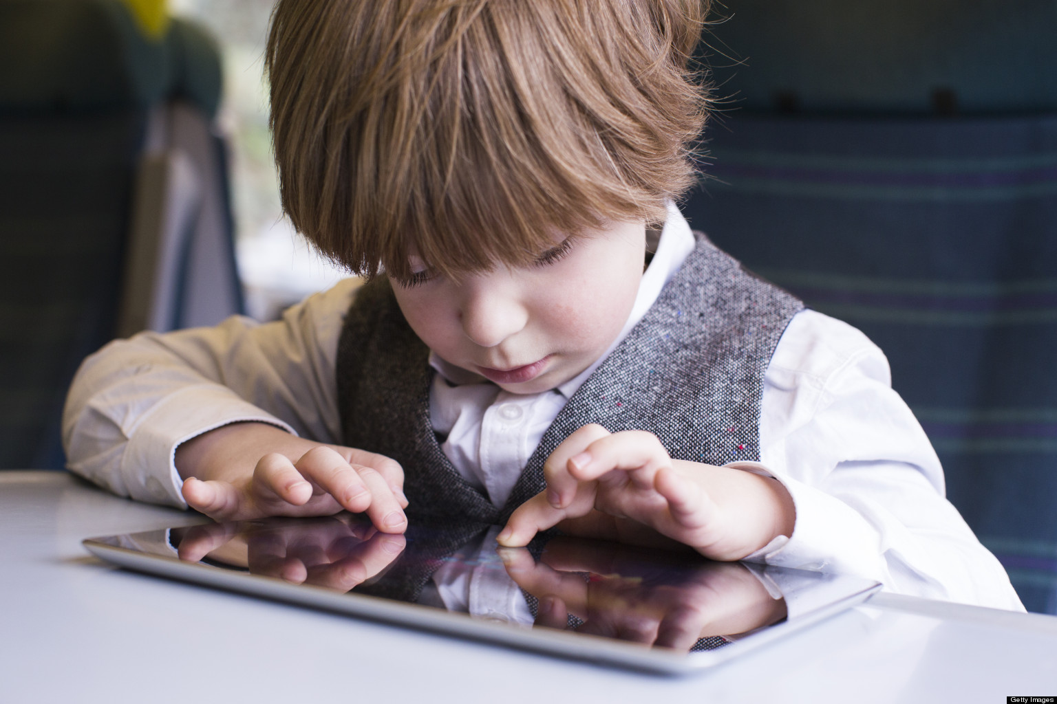Young boy travels with tablet on train