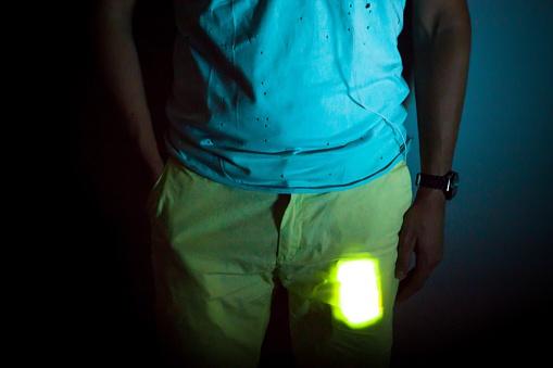 Smartphone lit on pocket of man at night.