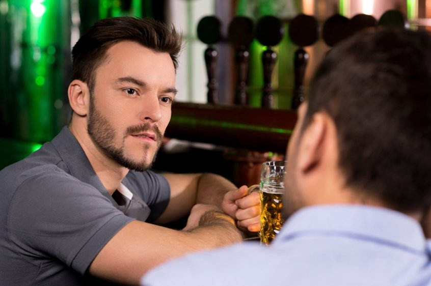 Spending time in bar. Two young men talking to each while drinking beer in bar