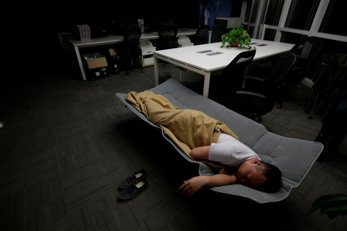 ma-zhenguo-a-systems-engineer-at-renren-credit-management-co-sleeps-on-a-camp-bed-at-the-office-after-finishing-work-in-the-early-morning