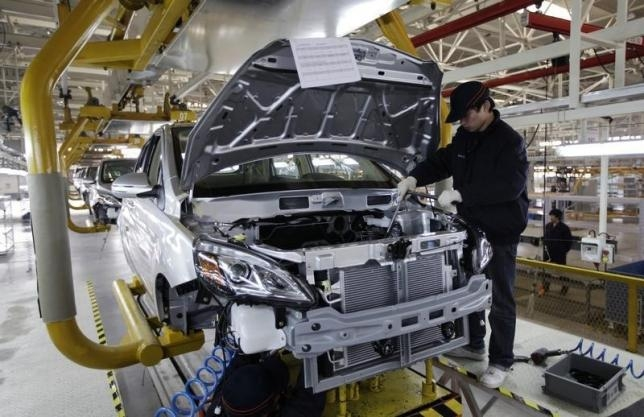 a-worker-checks-an-electric-car-in-an-ev-manufacturing-plant-in-beijing
