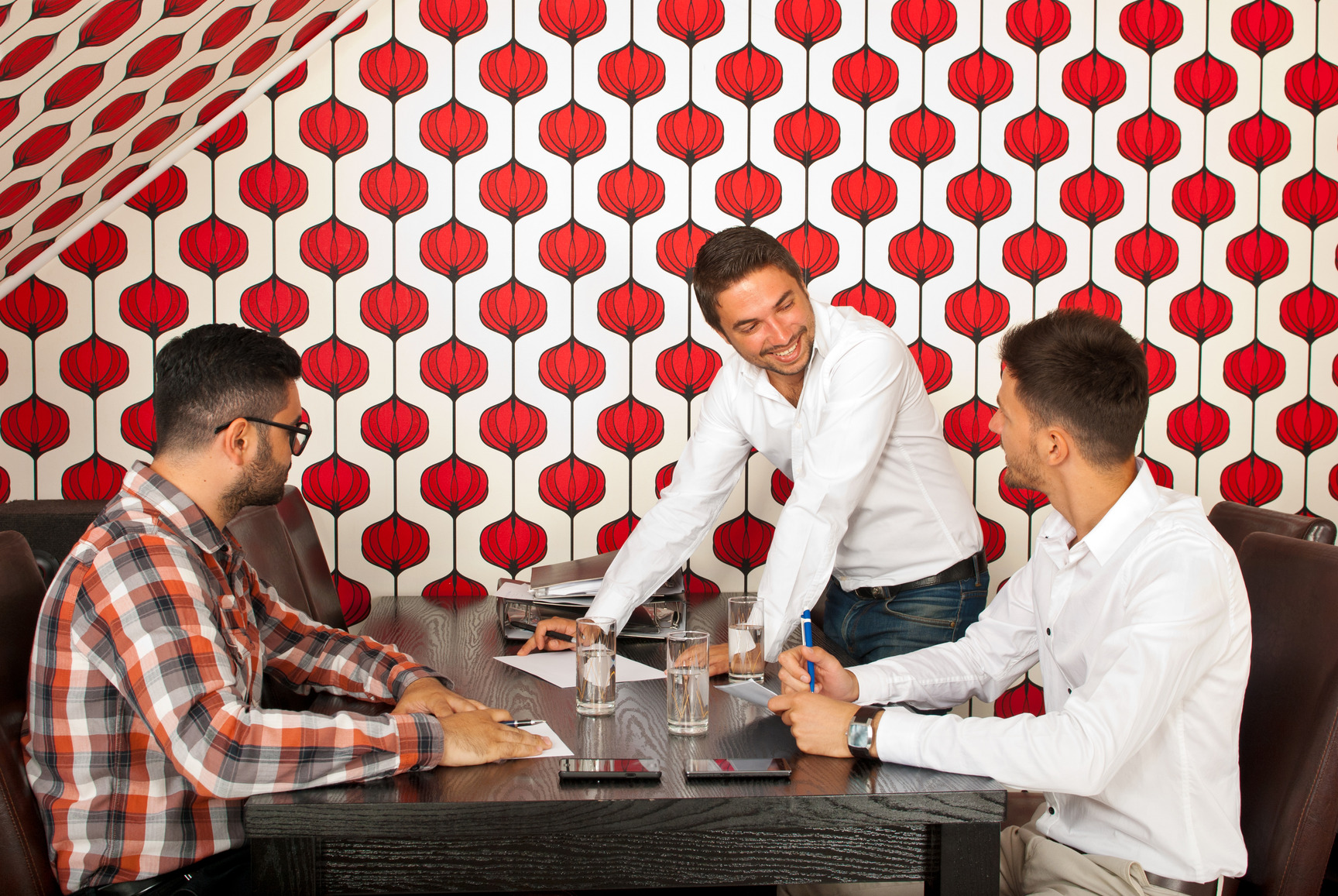 Three men having happy discussion at meeting in modern office
