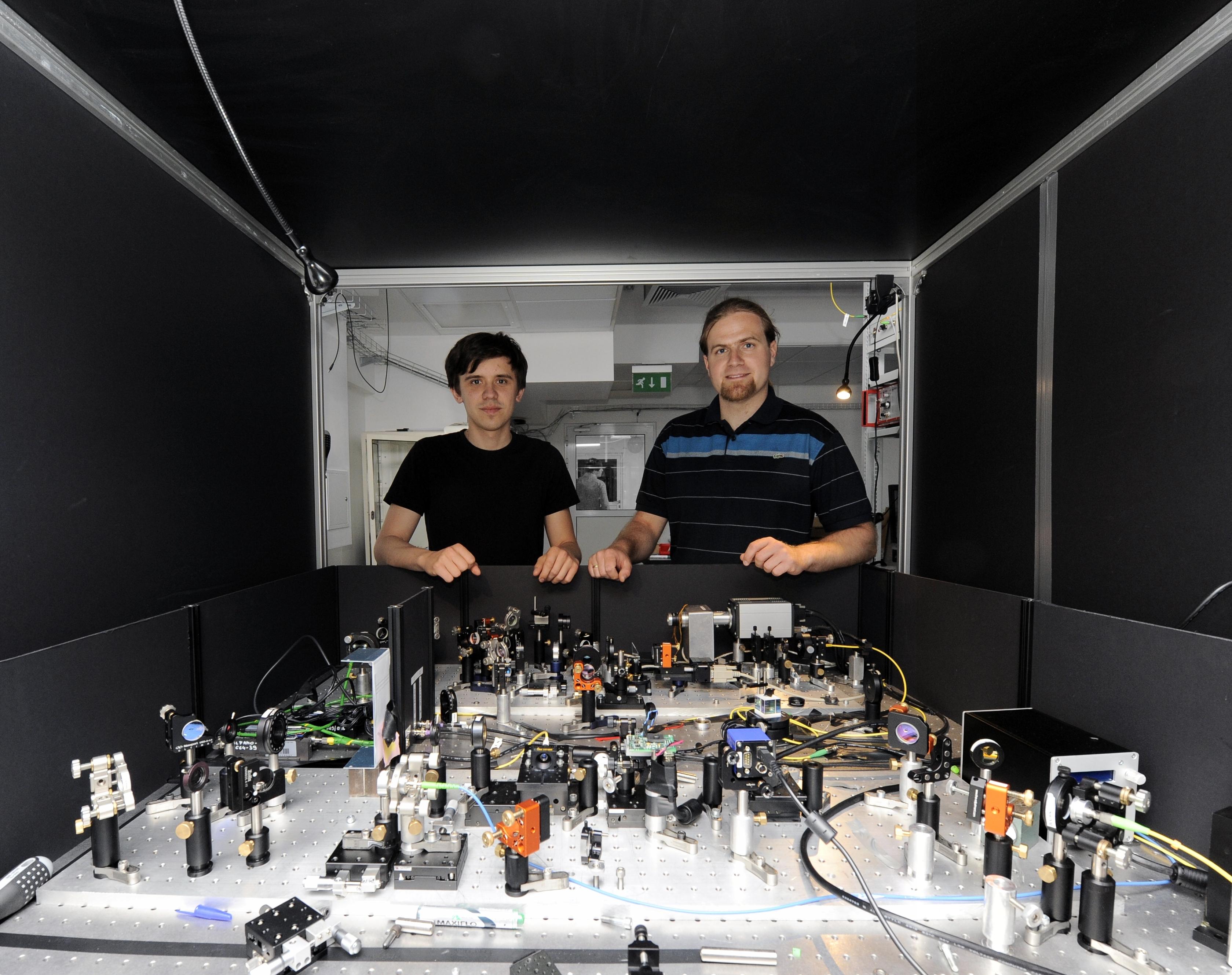 Dr. Radoslaw Chrapkiewicz (right) and doctoral student Michal Jachura at the apparatus for registration of holograms of single photons at the Faculty of Physics, University of Warsaw. (Source: FUW, Grzegorz Krzy¿ewski) Dr Rados³aw Chrapkiewicz (po prawej) i doktorant Micha³ Jachura przy aparaturze do rejestrowania hologramów pojedynczych fotonów na Wydziale Fizyki Uniwersytetu Warszawskiego. (ród³o: FUW, Grzegorz Krzy¿ewski)
