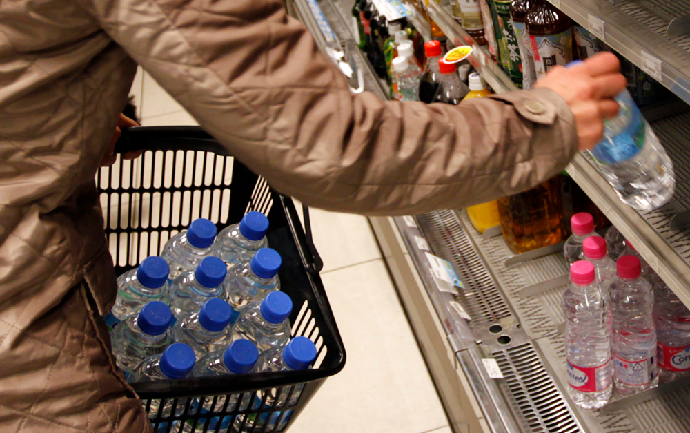 A woman buys bottled water imported from France at a convenience store in central Tokyo March 23, 2011. Japanese authorities advised against allowing infants to drink tap water in Tokyo due to raised radiation levels and the United States became the first nation to block some food imports from Japan. The crisis at the tsunami-smashed nuclear power plant, 250 km (150 miles) north of the Japanese capital, appeared far from over with workers attempting to gain control ordered to leave the site after black smoke began rising from one of its six reactors. The plant was crippled by a 9.0 magnitude earthquake and tsunami on March 11. REUTERS/Lee Jae-Won (JAPAN - Tags: DISASTER ENVIRONMENT HEALTH)