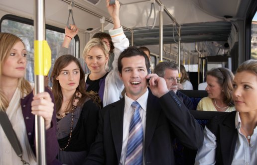 Businessman using mobile phone, laughing on bus