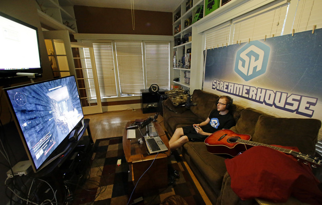 In this Nov. 6, 2014 photo, Robert Schill plays video games in his living room, in Lakeland, Fla. Schill plays video games nine to five, seven days a week and gets paid for it. (AP Photo/John Raoux)