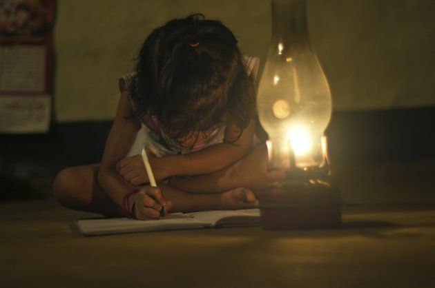 Village Girl reading book in lighting lamp