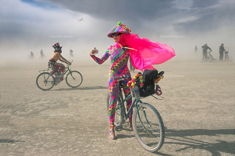 A wildflower blooms in the Black Rock Desert as California costume designer Jeanne Lauren braves a sandstorm at Burning Man, the annual weeklong festival in northwestern Nevada's National Conservation area. Beyond, Uncle Sam wheels along the vast playa, one of Earth's flattest spots. Over 26,000 people create an instant city that celebrates art in a unique counter-cultre experience.