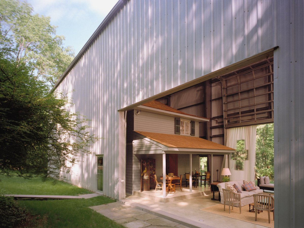 The airplane hangar encapsulates the historic farmhouse.