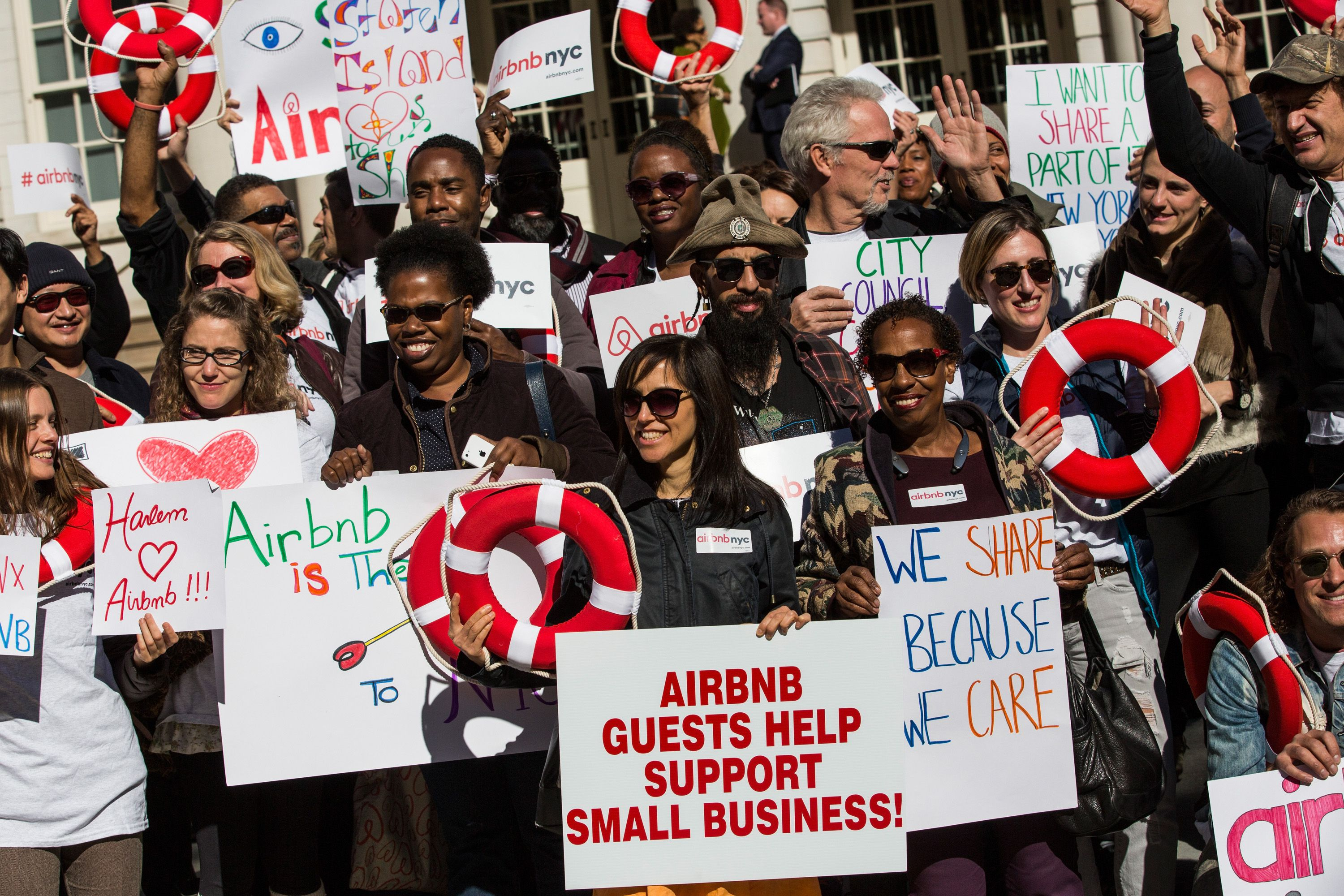 NEW YORK, NY - OCTOBER 30: Supporters of Airbnb hold a rally on the steps of New York City Hall showing support for the company on October 30, 2015 in New York City. The New York City council is currently debating how to regulate the controversial company. (Photo by Andrew Burton/Getty Images)
