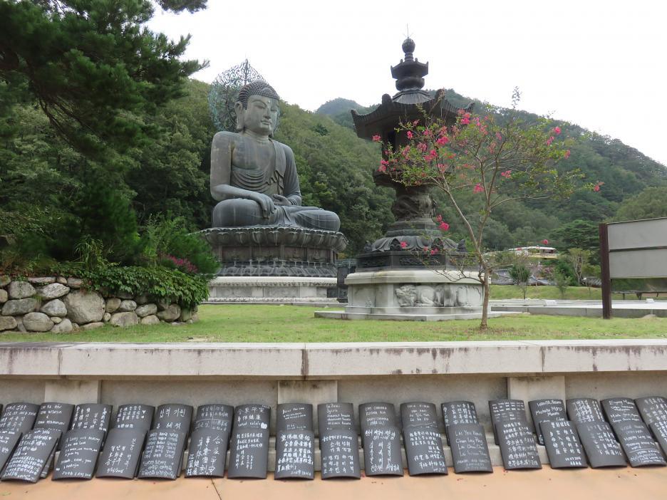 Socha Budhu pri vstupe do Národného parku Seoraksan. Mená donátorov sú uvedené na škridliach, poukladaných pod múrikom.