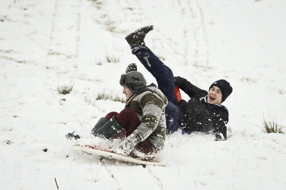 Friends enjoy sledging on Brecon Beacons, South Wales, where snow is settling and even more has been forecast by the MET office for Friday 18th January over South Wales and the Westcountry. PRESS ASSOCIATION Photo. Picture date: Thursday January 17, 2013. See PA story WEATHER Snow. Photo credit should read: Ben Birchall/PA Wire