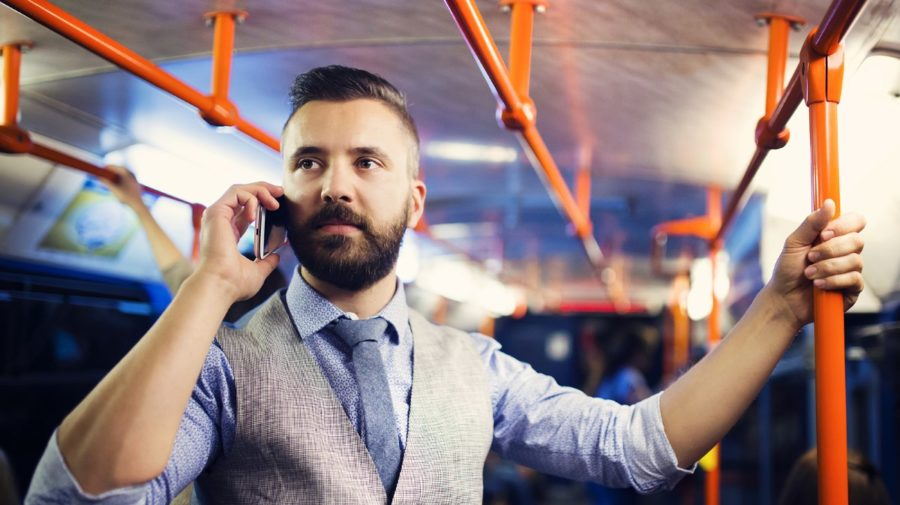 Handsome hipster modern man calling by mobile phone in tram in night