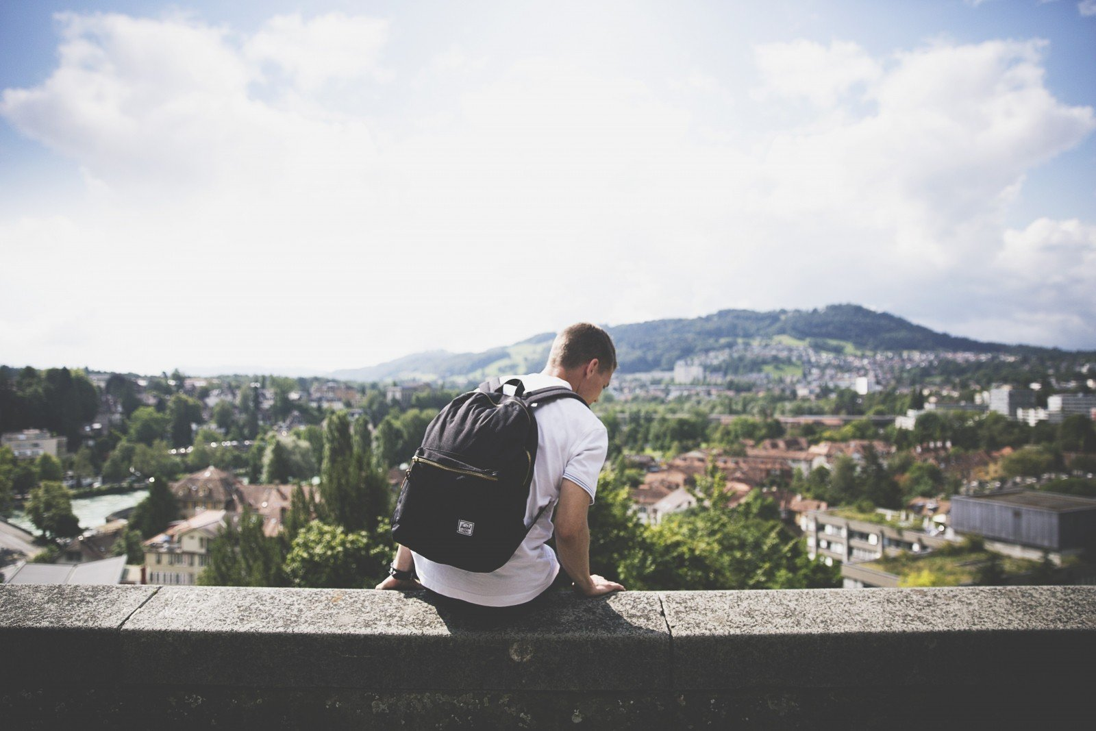 backpacker-sitting-on-wall-and-looking-down-on-town