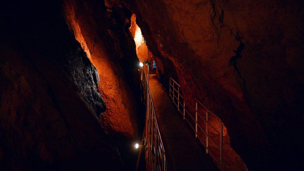 Ochtinská aragonitová jaskyňa je sústava priepastí a útesov, popretkávaná malými mostíkmi s tlmeným osvetlením.