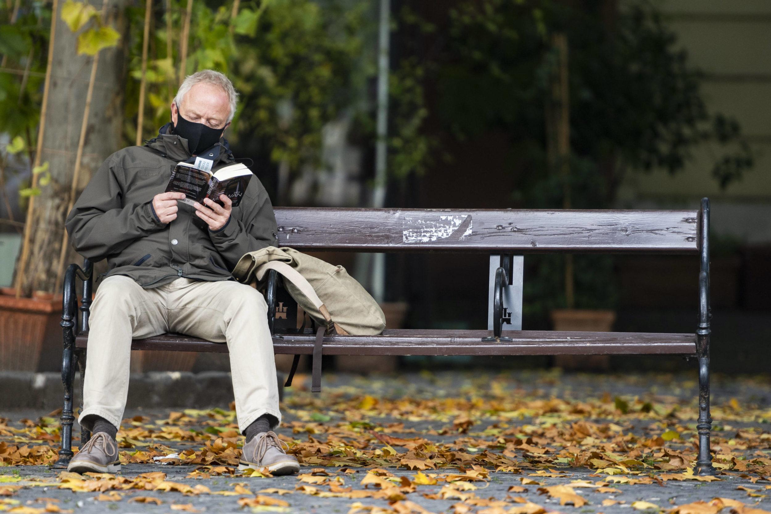Od soboty 24.októbra až do nedele 1. novembra 2020 platí na celom Slovensku zákaz vychádzania s výnimkou ciest na testovanie, do práce, cesty na výkon podnikateľskej činnosti alebo inej obdobnej činnosti či zabezpečenia nevyhnutných potrieb, či pobytu v prírode v okrese bydliska. Na snímke muž číta knihu na lavičke na Hviezdoslavovom námestí v Bratislave 26. októbra 2020. FO